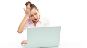 Upset woman looking at her laptop